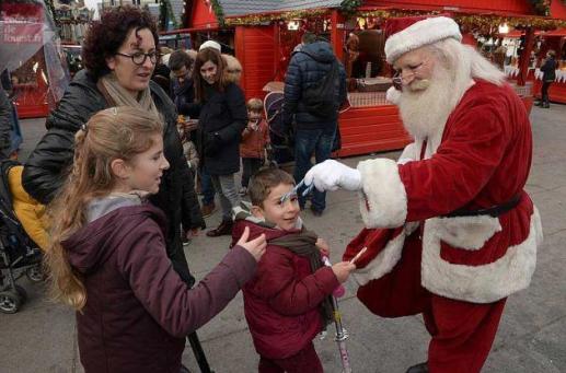 Le Père-Noël avec des enfants au Marché de Noël d'Angers